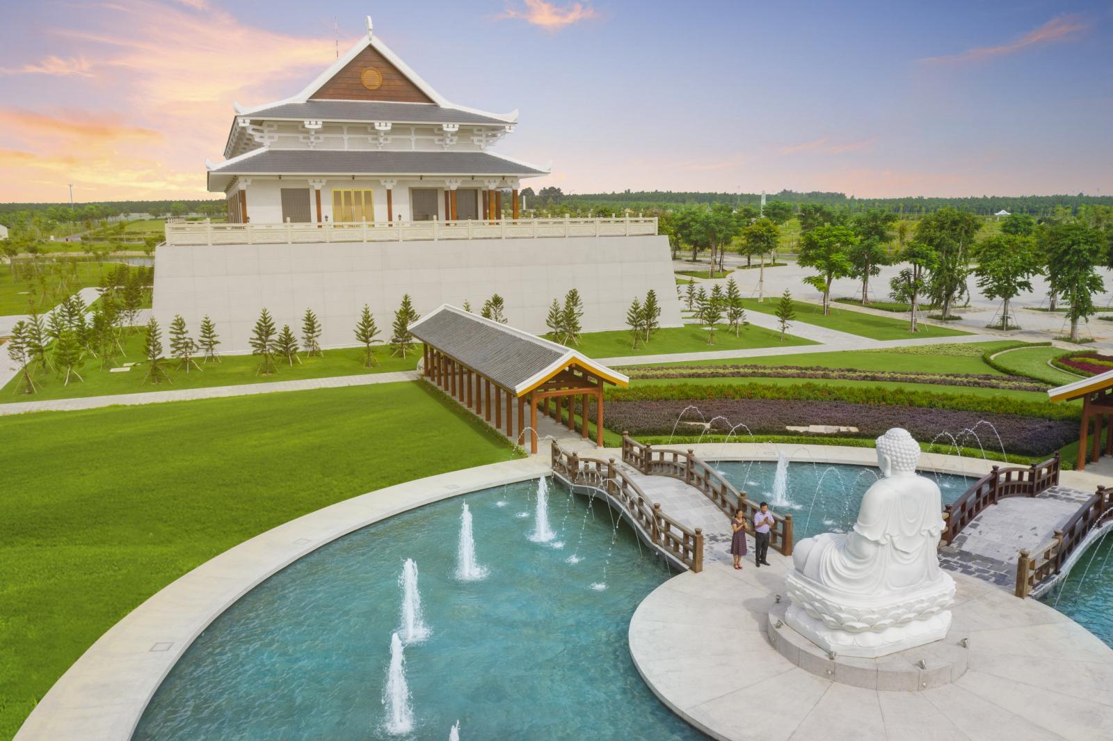 Tượng phật đặt giữa đài phun nước đối diện ngôi đền, có hai người đang đứng chắp tay trước tượng phật