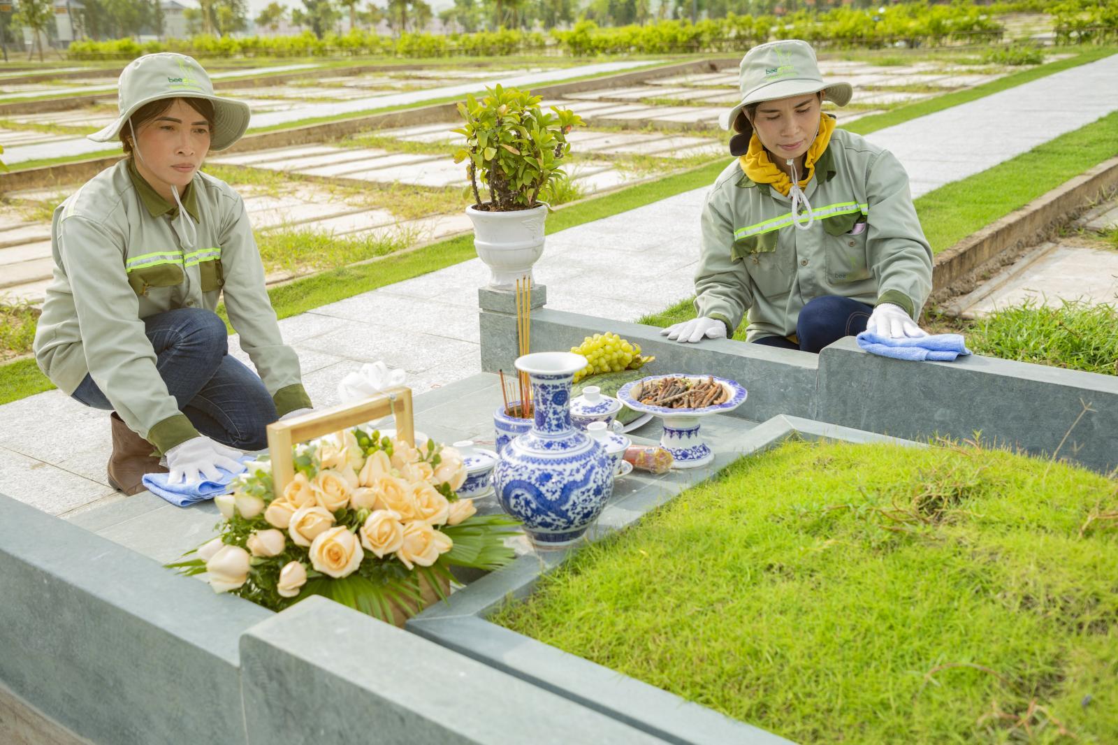 Hai người phụ nữ đang ngồi lau dọn phần mộ