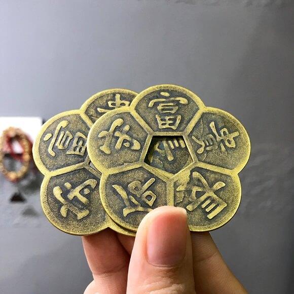 bàn tay cầm hai đồng tiền hình bông hoa mai chồng lên nhau.