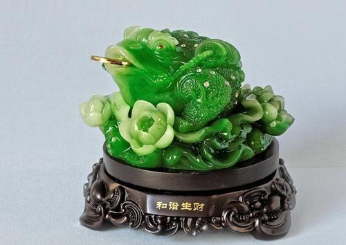 Tượng cóc thiềm thừ bằng ngọc màu xanh miệng ngậm đồng tiền, ngồi trên hoa sen và một giá đỡ bằng gỗ màu nâu.