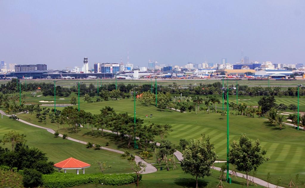 một khu đất trống, phía xa là những tòa nhà cao tầng