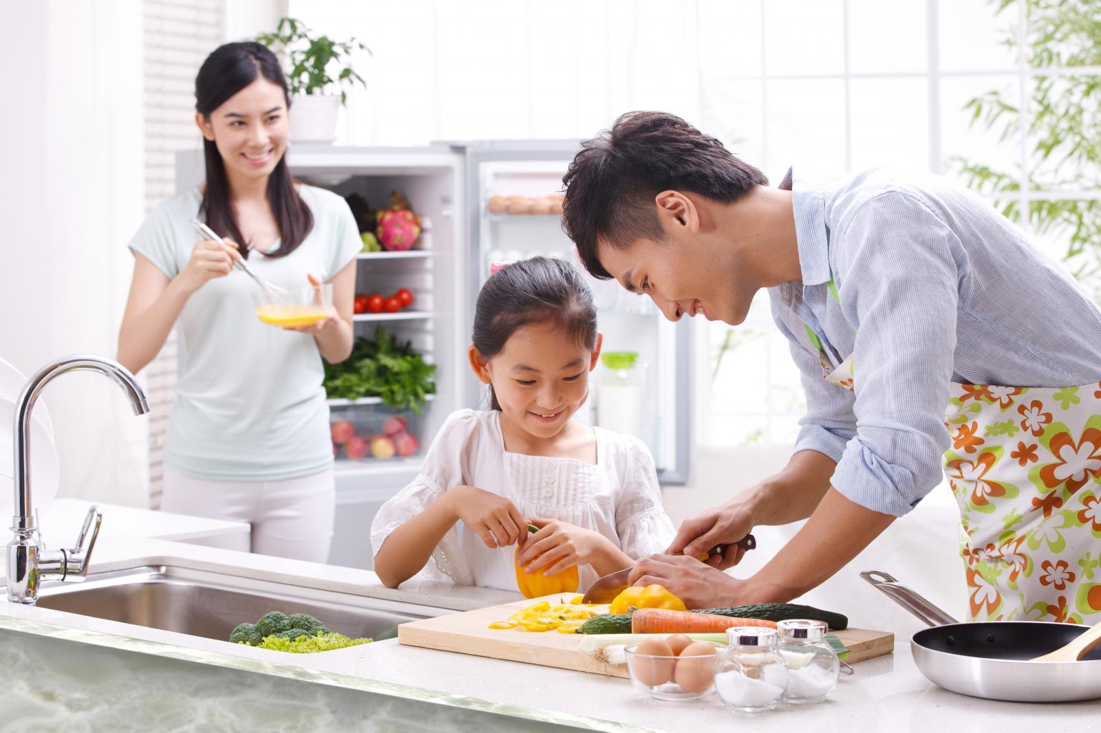 ba người hai lớn một bé đang nấu ăn trong khu bếp.