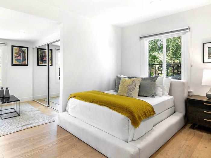 phòng ngủ màu trắng với chăn, gối màu vàng