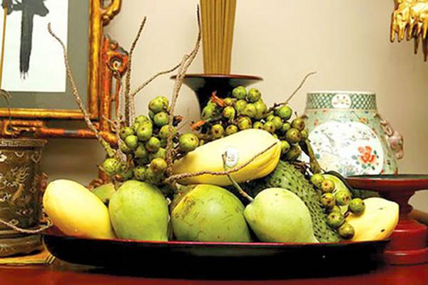 Đĩa trái cây lớn trên bàn thờ gồm nhiều loại quả màu xanh.