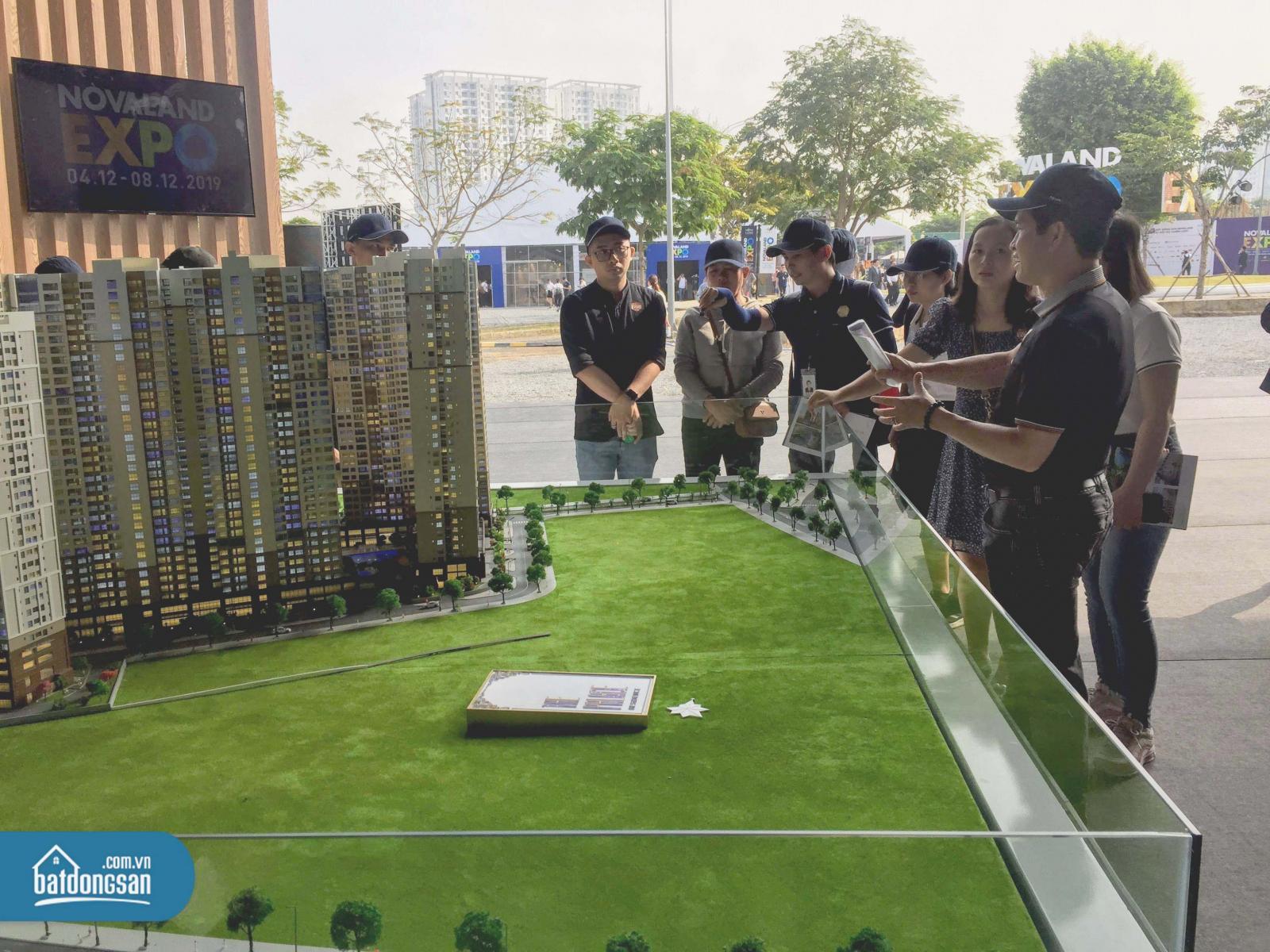 Một nhóm người đứng quanh sa bàn dự án bất động sản là những tòa nhà cao tầng nằm trên bãi cỏ.