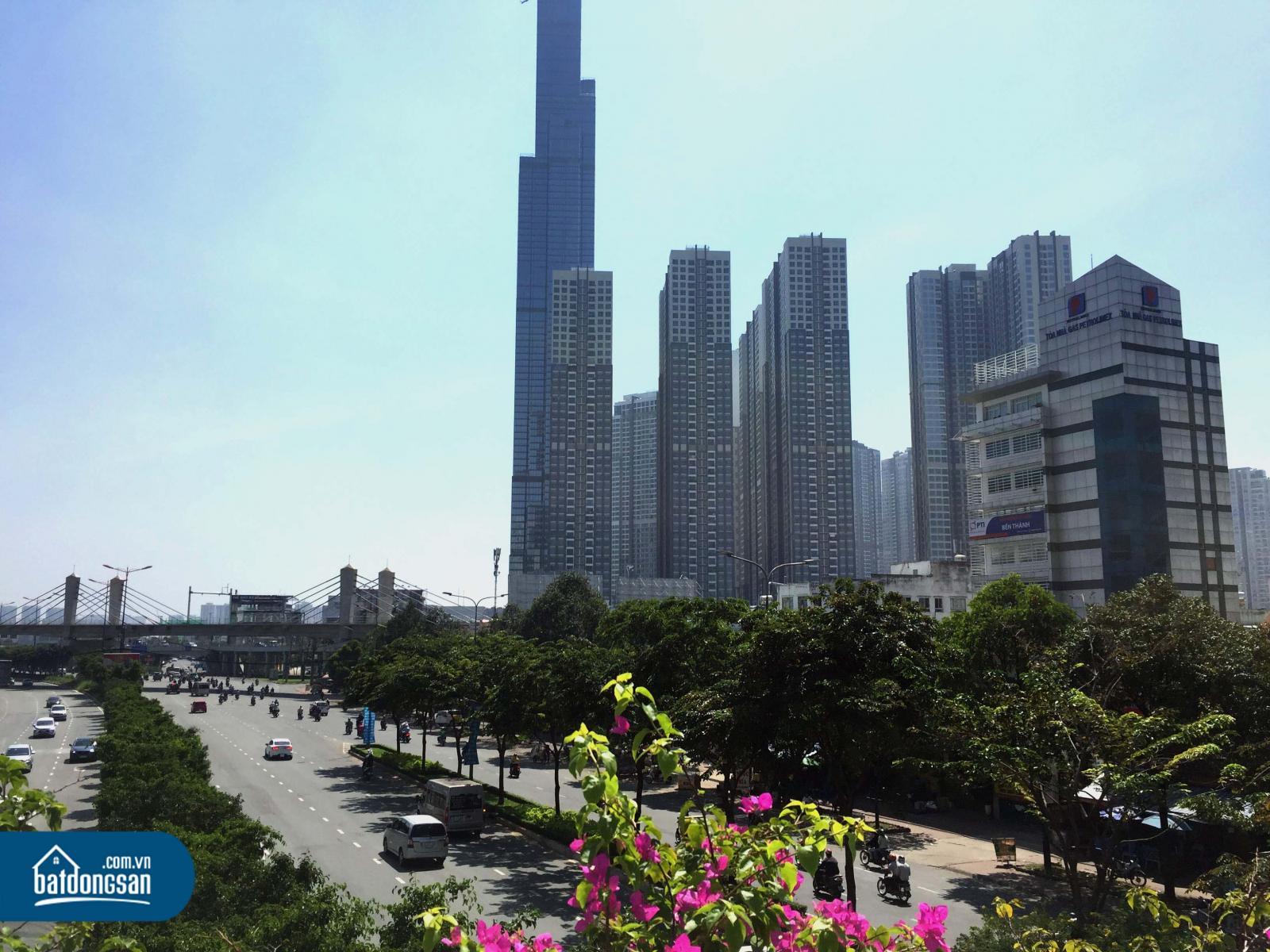 Con đường lớn nhiều làn xe có các hàng cây, bên cạnh là những tòa nhà cao tầng.