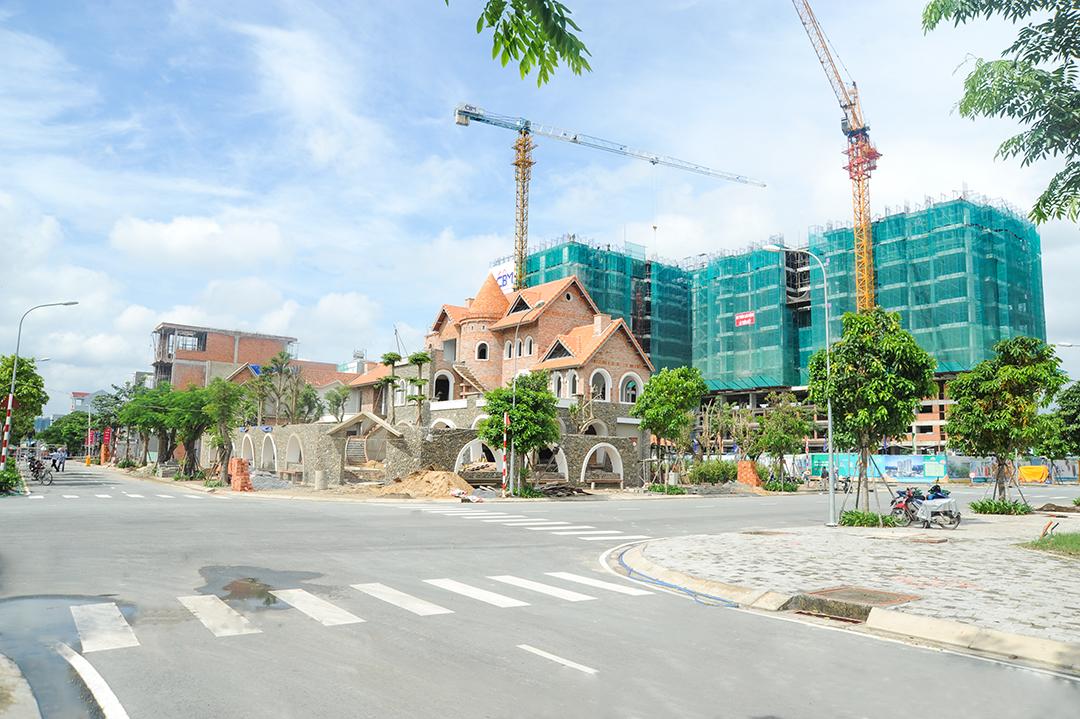 các công trình nhà ở cao tầng và thấp tầng nằm cạnh đường lớn đang được xây dựng