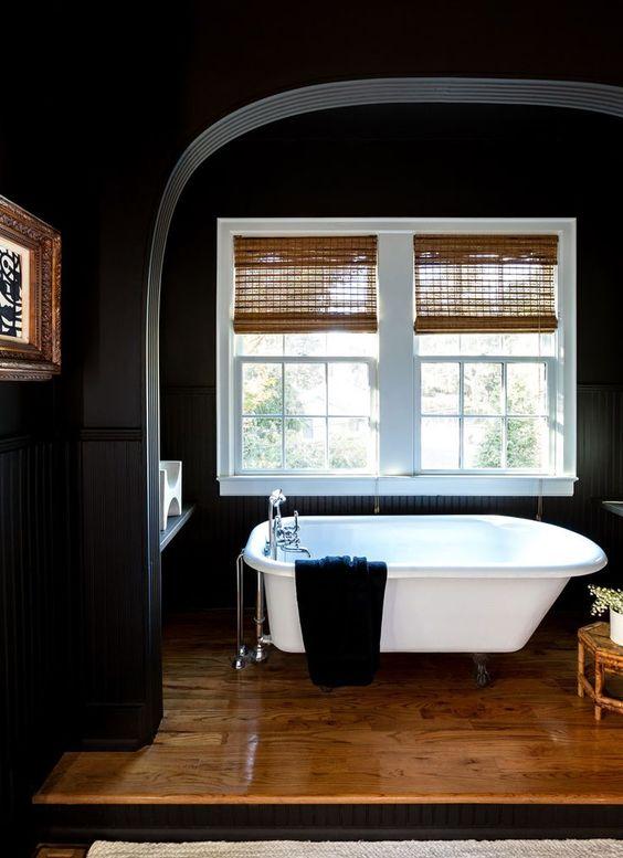 phòng tắm tối màu với bồn tắm sứ màu trắng