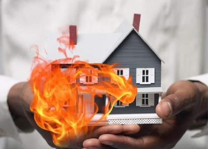 hai bàn tay cầm mô hình ngôi nhà, bên cạnh ngôi nhà có hình ngọn lửa bốc cháy