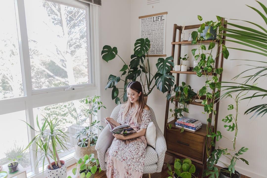 cô gái ngồi đọc sách ở góc thư giãn với rất nhiều cây xanh