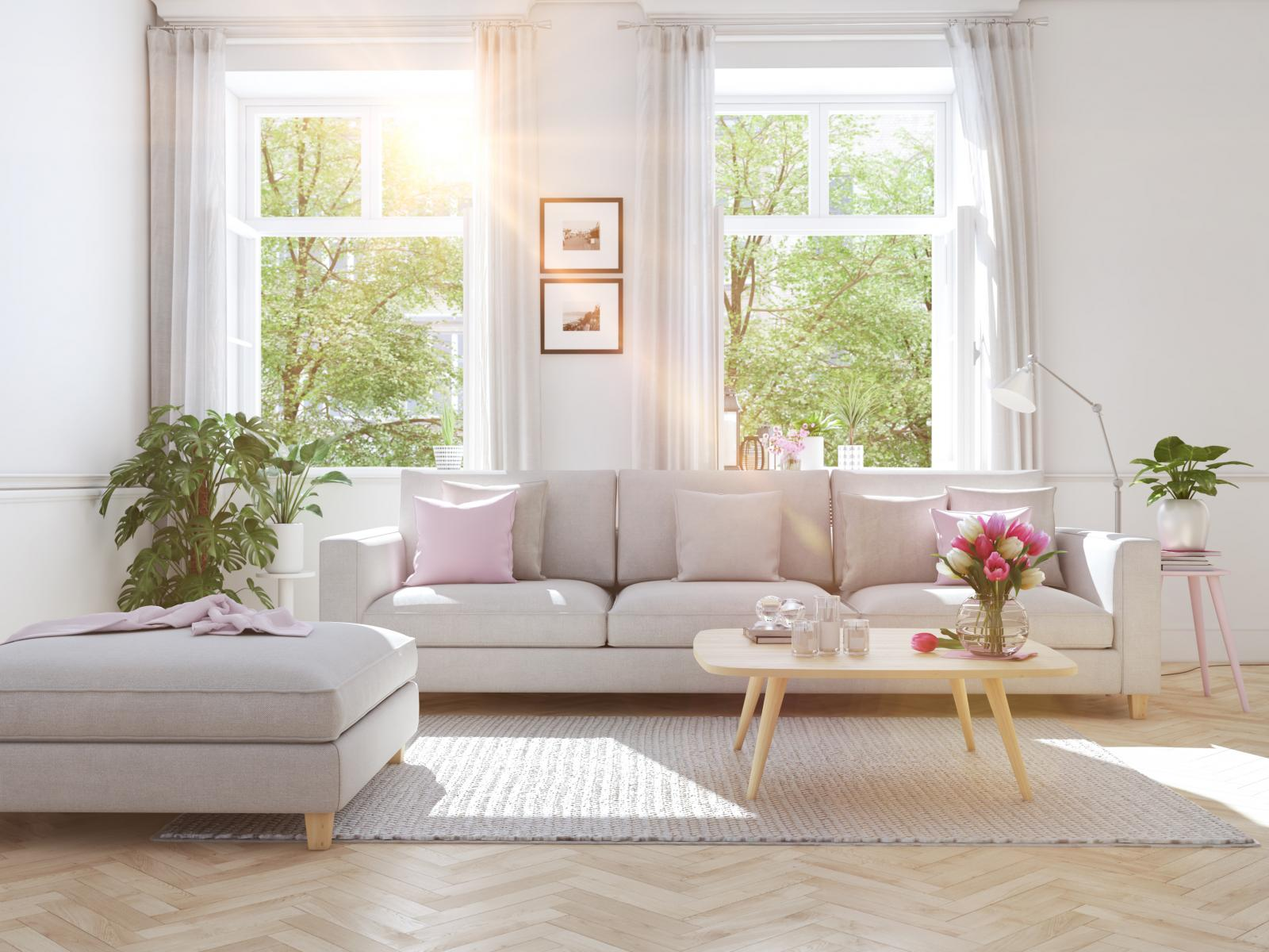 Phòng khách màu trắng với sofa trắng, lọ hoa trên bàn... đặt cạnh cửa sổ nhiều ánh nắng.