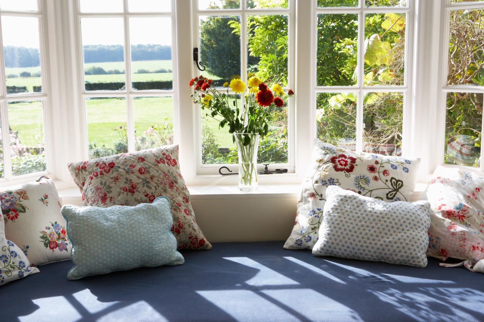 Ghế sofa có nhiều gối ôm đặt cạnh khung cửa sổ kính trắng nhìn ra bãi cõ, lọ hoa nhiều màu.