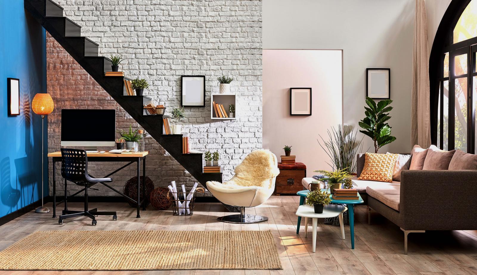Phòng khách với sofa, bàn trà, góc nhà cạnh bức tường trắng là cầu thang gỗ màu đen đặt nhiều chậu cây.