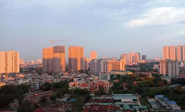 Một góc thành phố gồm nhiều tòa nhà cao tầng màu vàng nhạt và nhà ở thấp tầng