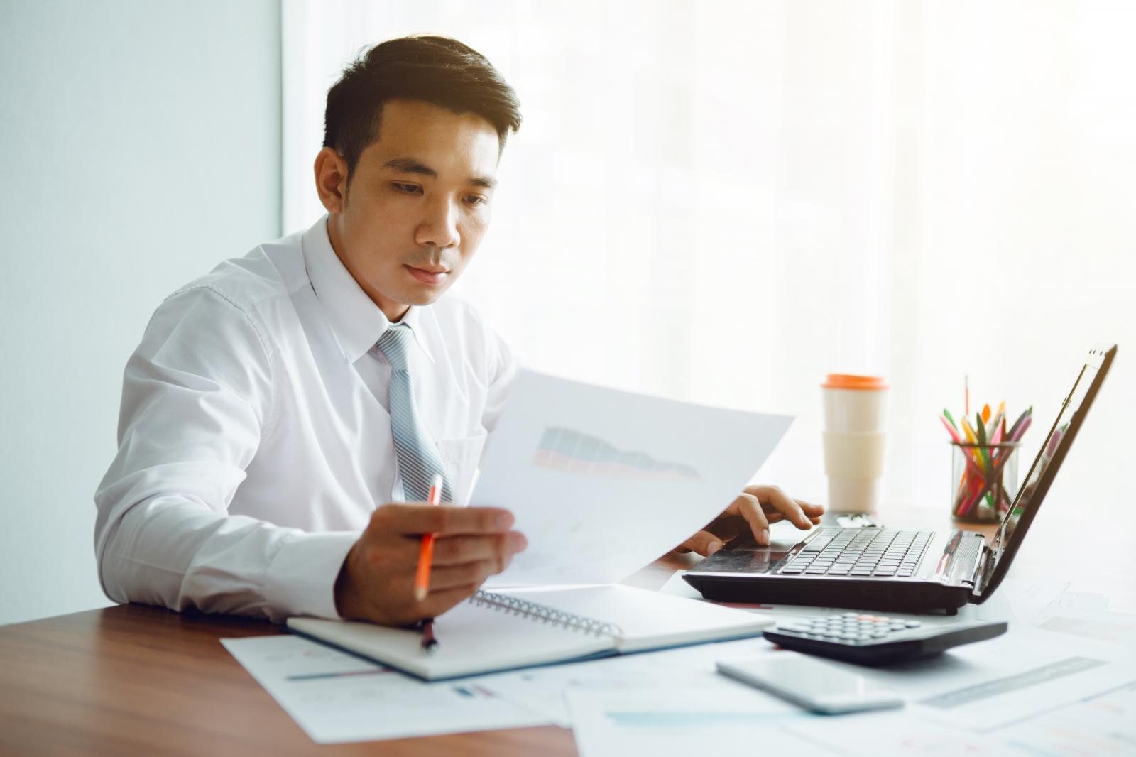 một người đàn ông tay cầm tờ giấy đang ngồi làm việc trên máy tính