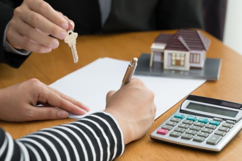 Bàn tay cầm bút đang viết trên giấy, một người khác cầm chìa khóa, bên cạnh là máy tính, mô hình ngôi nhà để trên bàn.