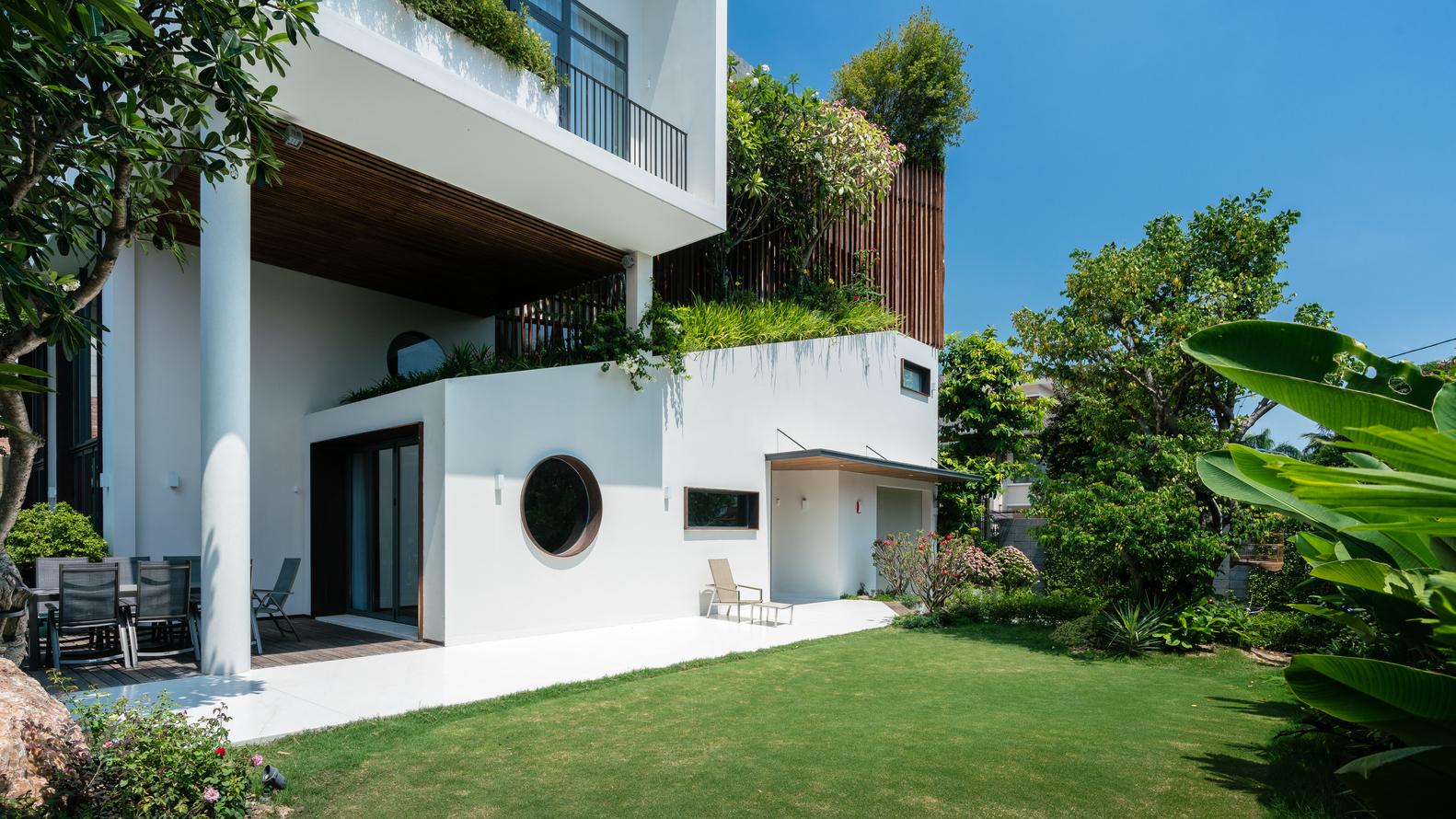thảm cỏ và cây xanh bên ngoài biệt thự
