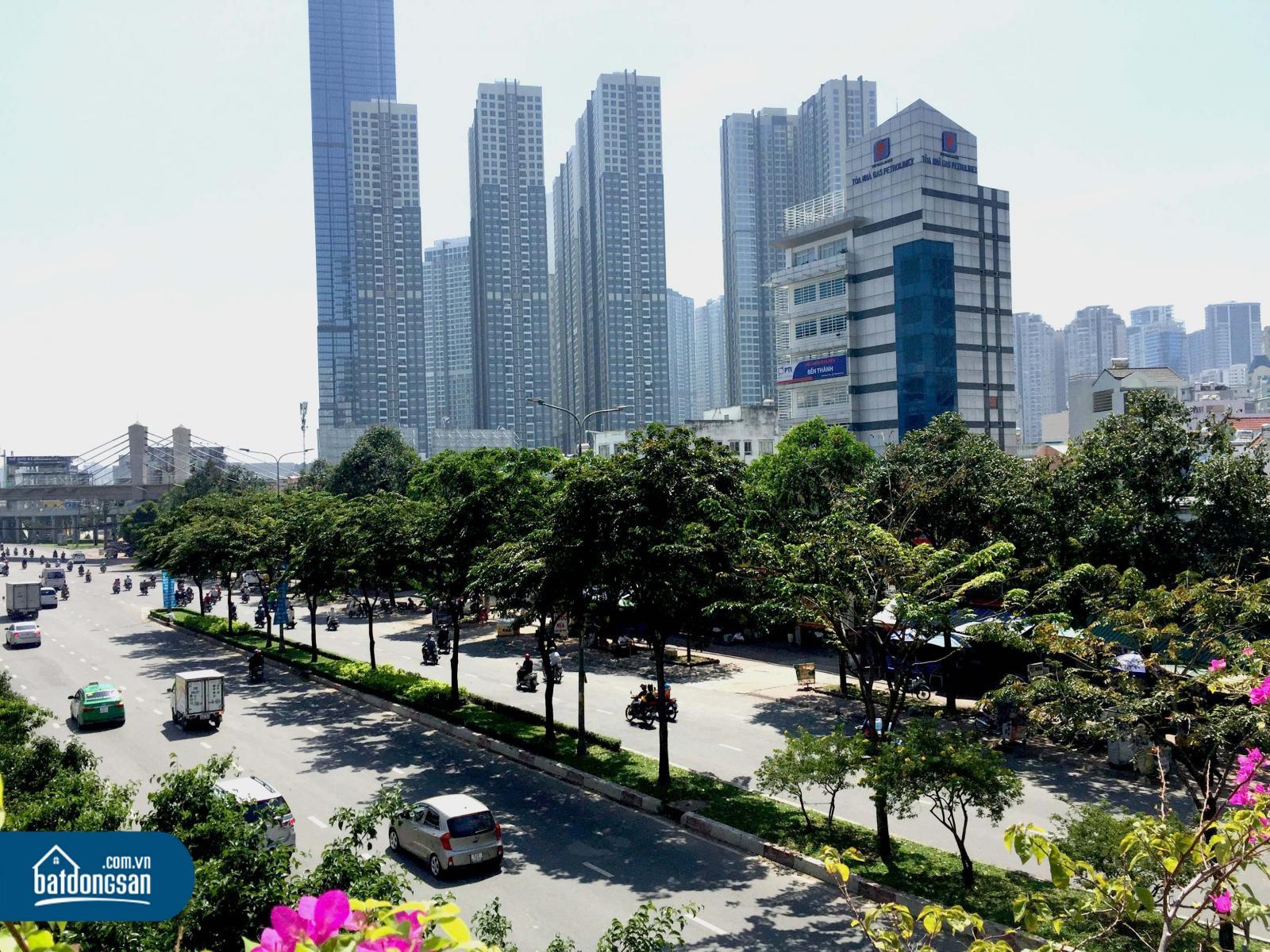 Con đường nhiều cây xanh, xe cộ, phía xa là những tòa nhà cao tầng san sát nhau.