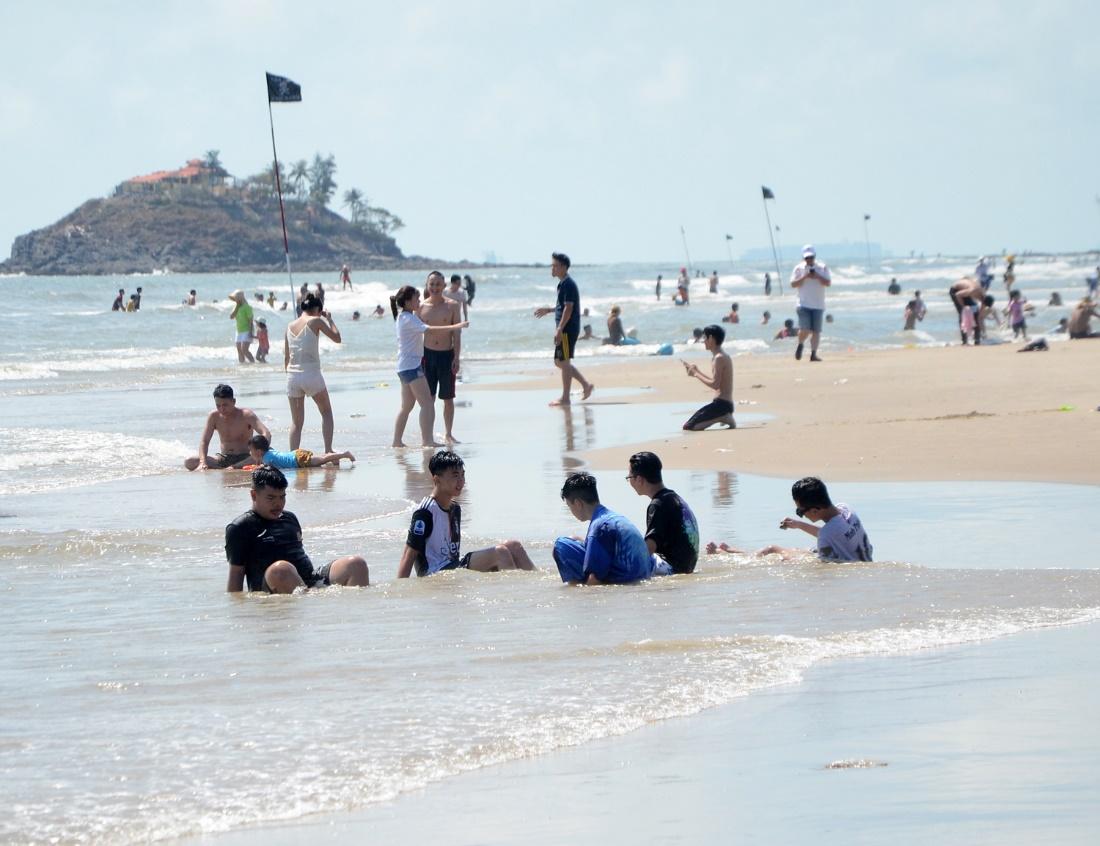 Nhiều khách du lịch đang ngồi, đi lại và tắm tại bãi biển