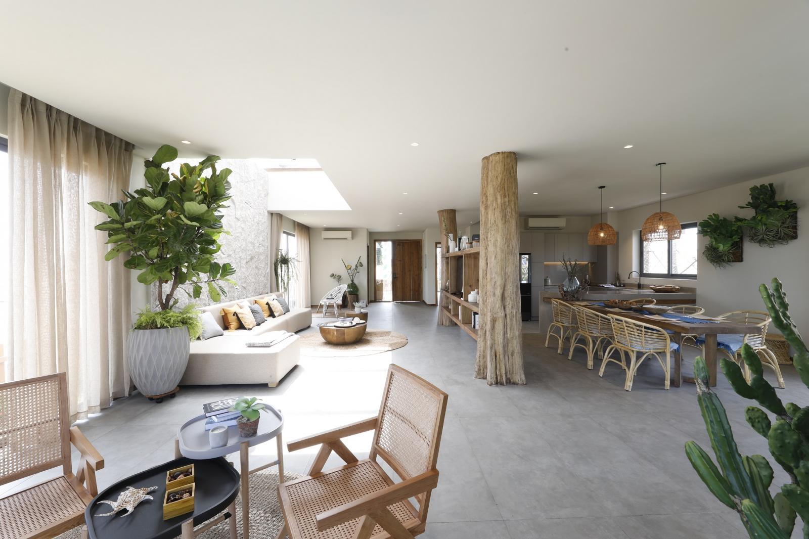 một góc căn nhà với những chiếc ghế mây, bàn tròn, ghế sofa trắng hình chữ L, chậu cây cảnh,...