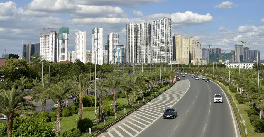 đại lộ Thăng Long có xe đang chạy, phía xa có nhiều tòa chung cư cao tầng