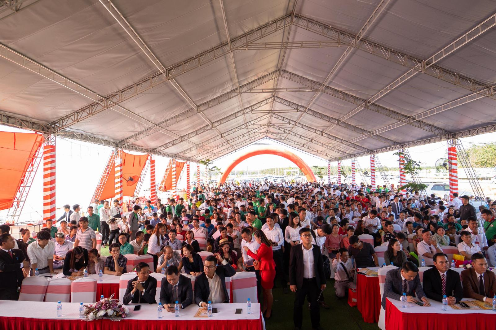 Rất nhiều người đang ngồi tham gia một sự kiện tổ chức ngoài trời có mái che