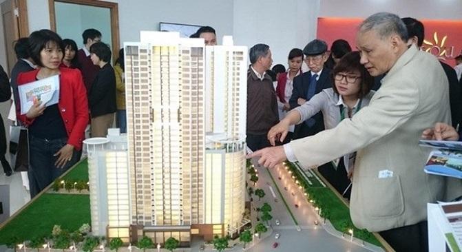 Nhiều người đang đứng xem một sa bàn dự án chung cư tại một công ty bất động sản.