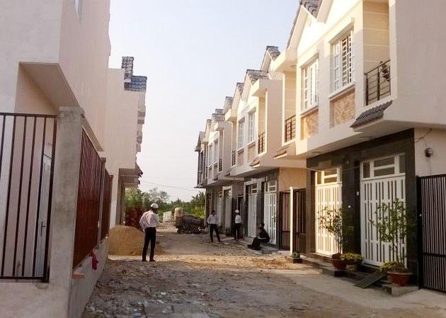 Hai dãy nhà xây sẵn nằm đối diện nhau, ở giữa lối đi có người đứng nghe điện thoại