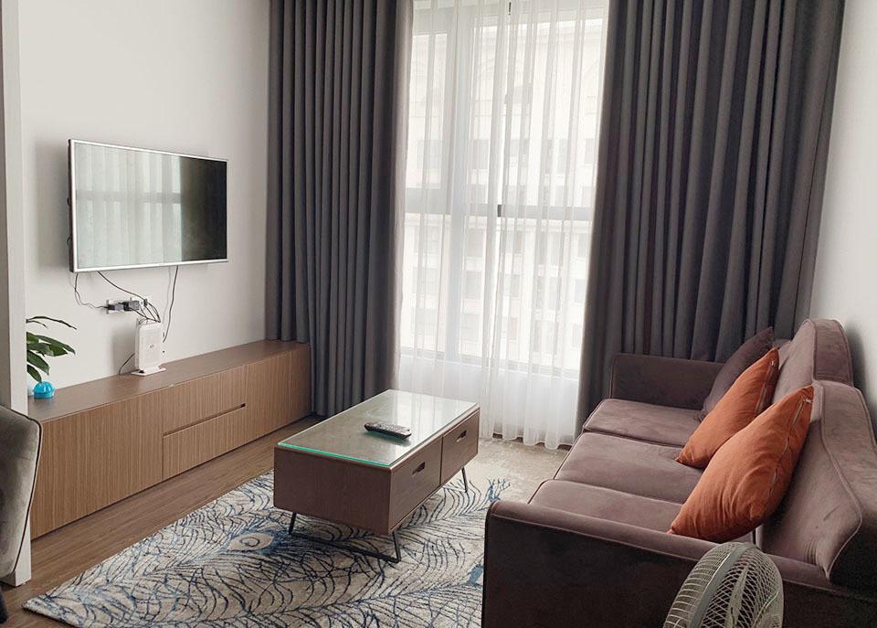 Phòng khách căn hộ chung cư với chiếc tivi treo tường, bàn ghế sofa, gối ôm màu cam, thảm trải sàn màu trắng xanh