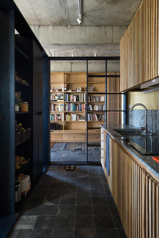 góc nấu nướng với tường xi măng vàng và tủ gỗ dán màu chàm