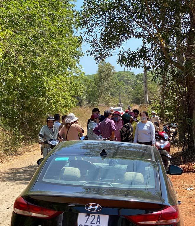 Nhóm đông người tụ tập phía trước một chiếc xe ô tô màu đen trao đổi thông tin mua đất tại Bình Ba