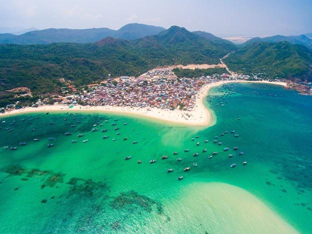 Ảnh chụp một bãi biển nước xanh biếc, bao quanh là đồi núi và khu dân cư