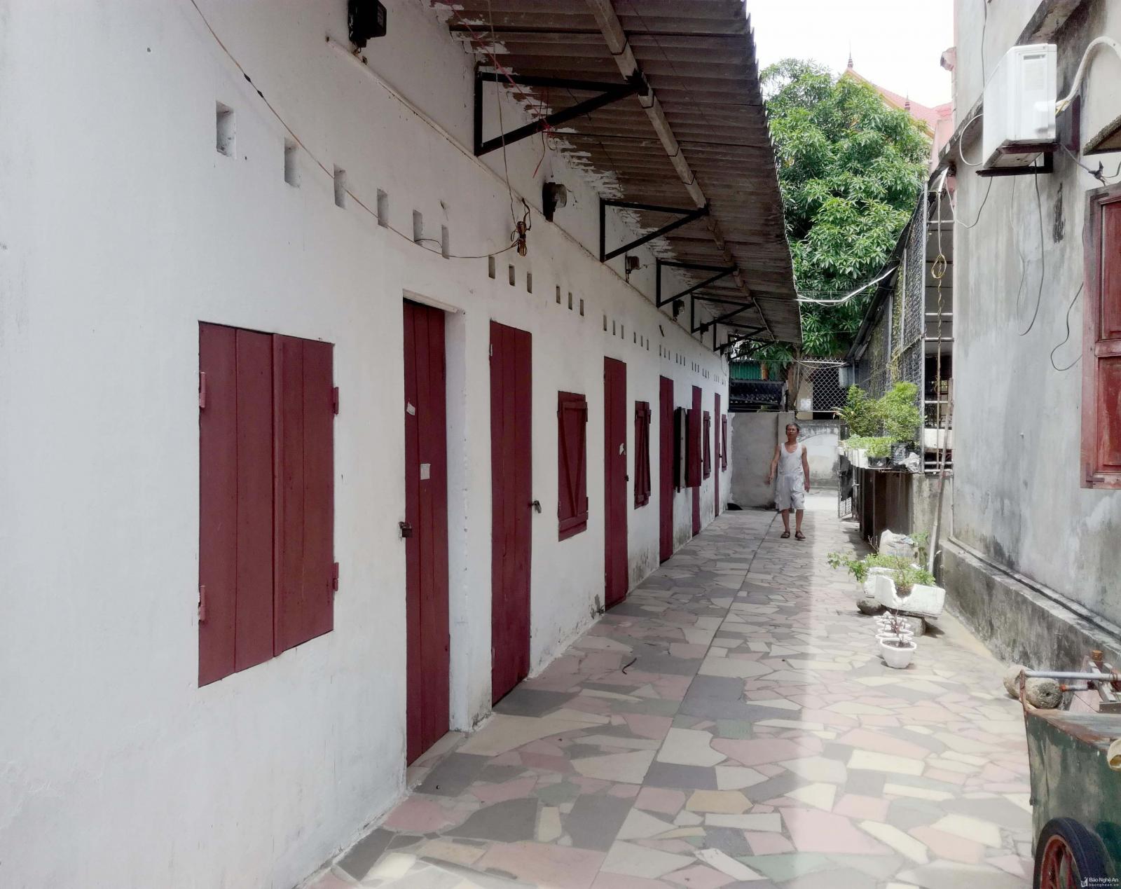 Một dãy nhà trọ cho thuê vắng vẻ, các phòng đóng kín cửa, một người đàn ông đi ở sân.