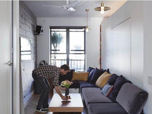 người đàn ông đang sắp xếp lại phòng khách trong căn hộ nhỏ