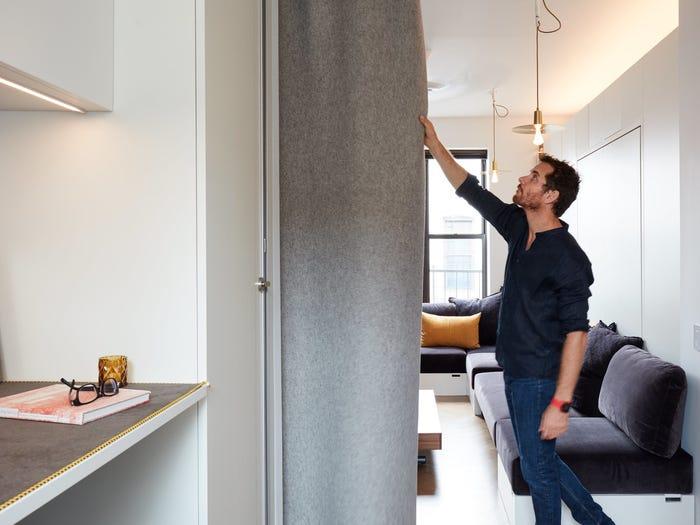 người đàn ông đang kéo rèm cửa