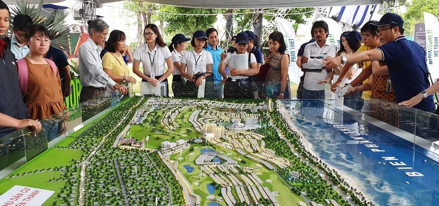 Môi giới bất động sản đang tư vấn cho các khách hàng đứng xem sa bàn một dự án bất động sản.