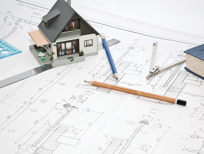 Mô hình một ngôi nhà đặt trên bản vẽ thiết kế nhà ở hợp phong thủy.