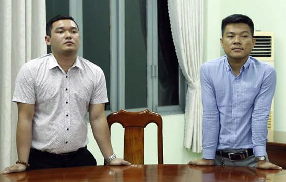 Hai thanh niên trẻ là giám đốc công ty bất động sản đứng cạnh bàn làm việc trước lúc bị bắt.