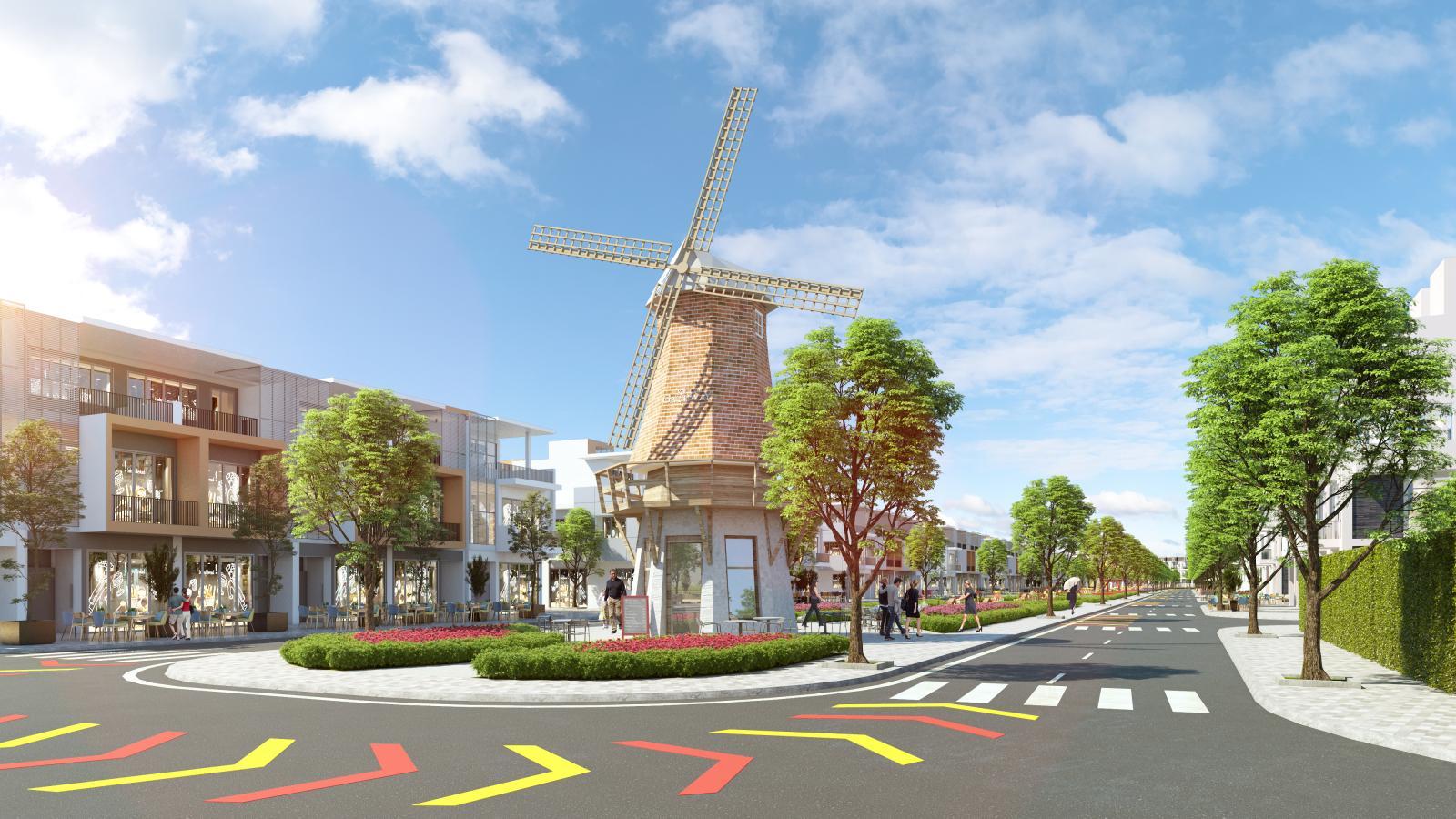 Một dãy nhà nằm gần mô hình cối xay gió và hàng cây xanh