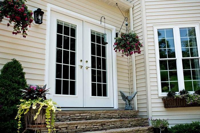Phía trước một ngôi nhà cấp 4 màu trắng, cửa chính sơn trắng, bên ngoài có nhiều hoa.