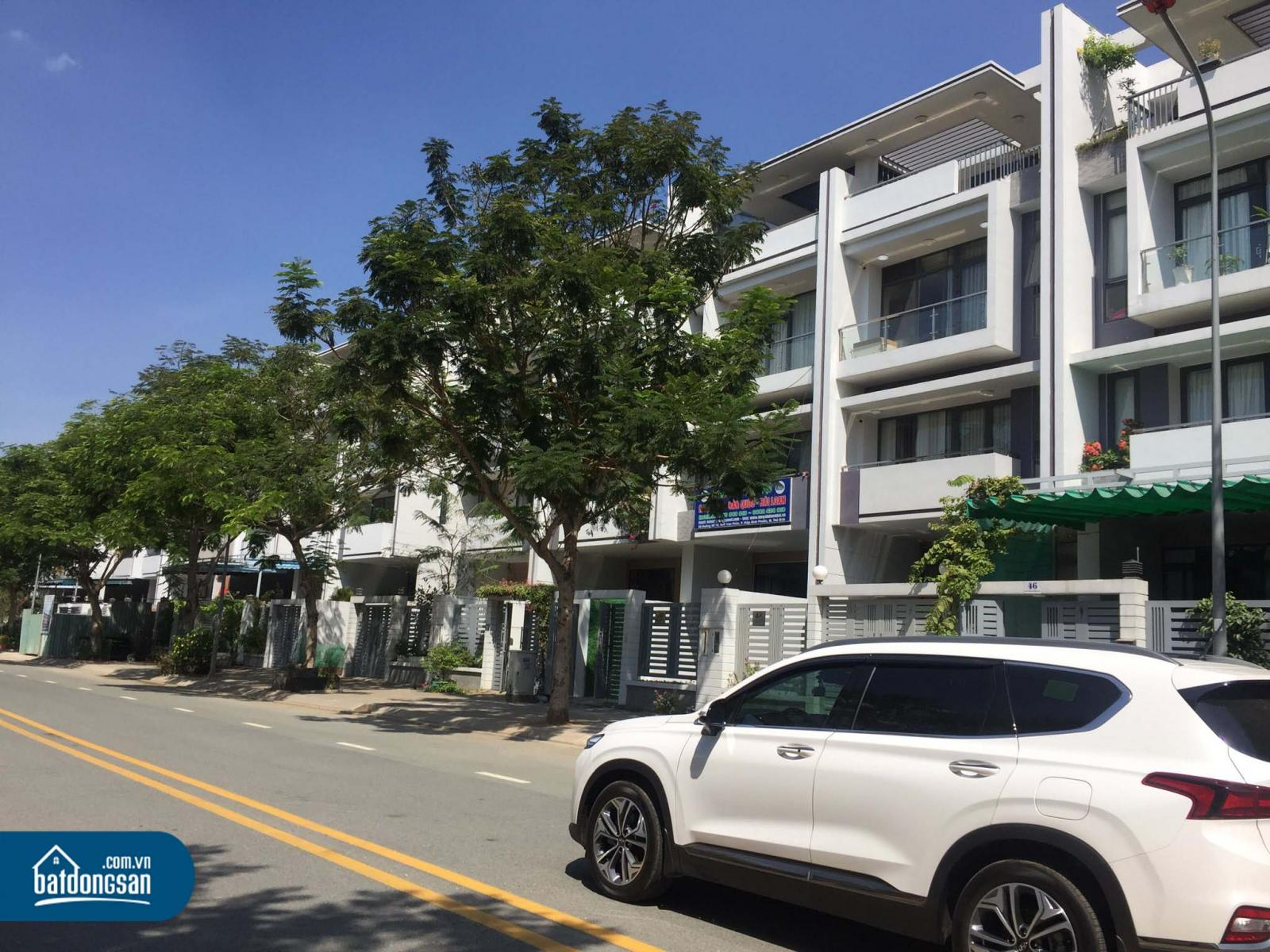 Dãy nhà liền kề nằm cạnh con đường lớn, cây xanh, ô tô màu trắng.