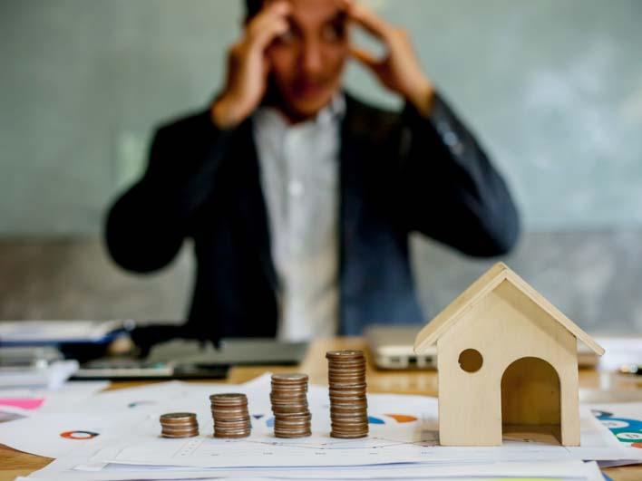 Người đàn ông mặc vest ngồi ôm đầu lo lắng ngồi ở bàn làm việc, bên trên bàn là mô hình ngôi nhà, giấy tờ hợp đồng đặt cọc mua bán đất...
