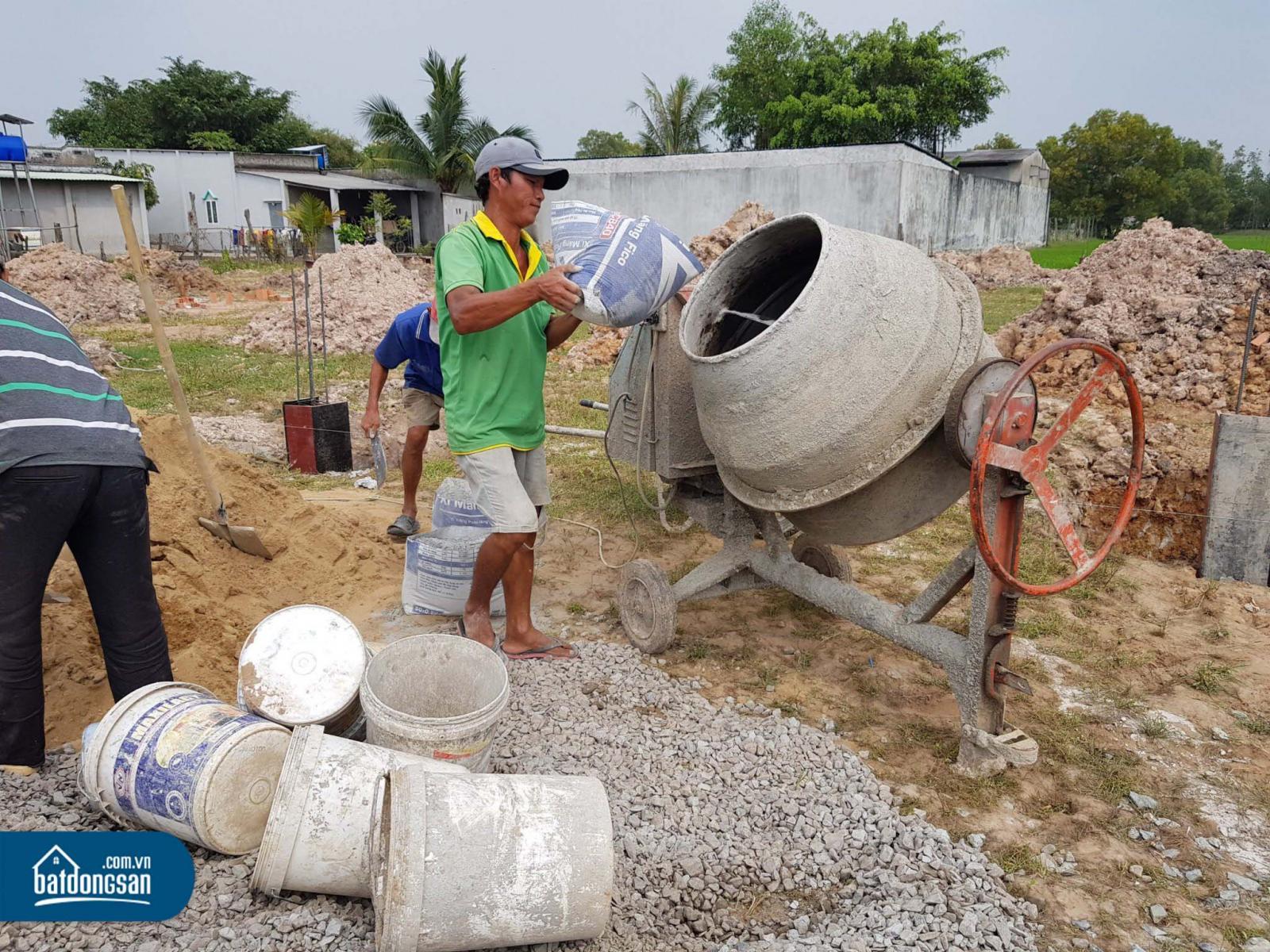 Ba nam công nhân đang đổ vật liệu vào máy trộn bê tông làm hạ tầng trong một dự án đất nền.