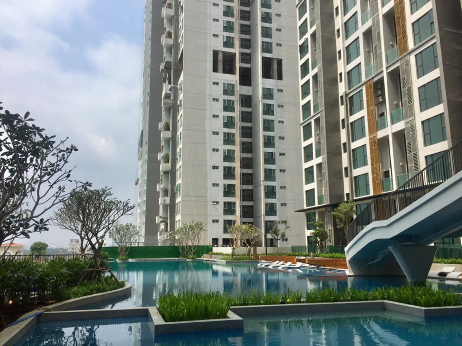 Bể bơi nước xanh trong phía dưới một tòa chung cư cao tầng.