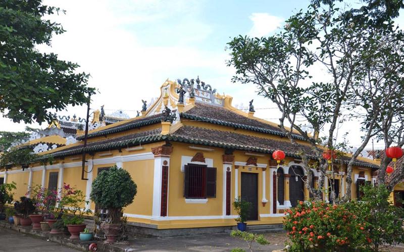 Kiến trúc đền miếu của miền Tây Nam Bộ với phần mái nhọn và sơn tường vàng, xung quanh nhiều cây cối.