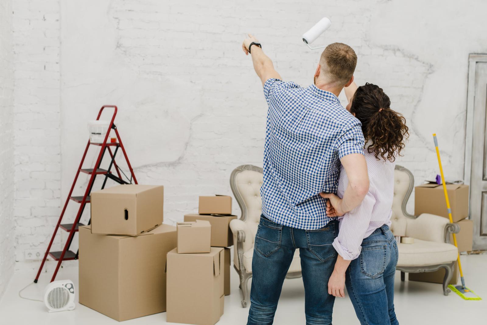 1 người đàn ông và 1 người phụ nữ đang chỉ vào bức tường của căn phòng, xung quanh là dụng cụ sửa chữa nhà