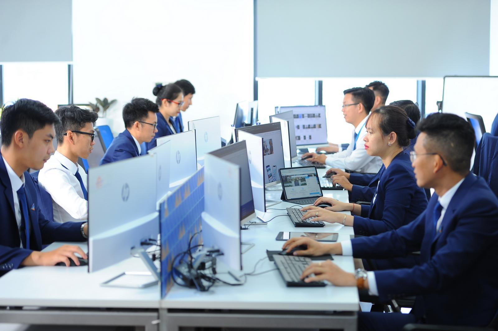 Nhiều nhân viên môi giới của Đất Xanh mặc vest ngồi làm việc bên máy tính.