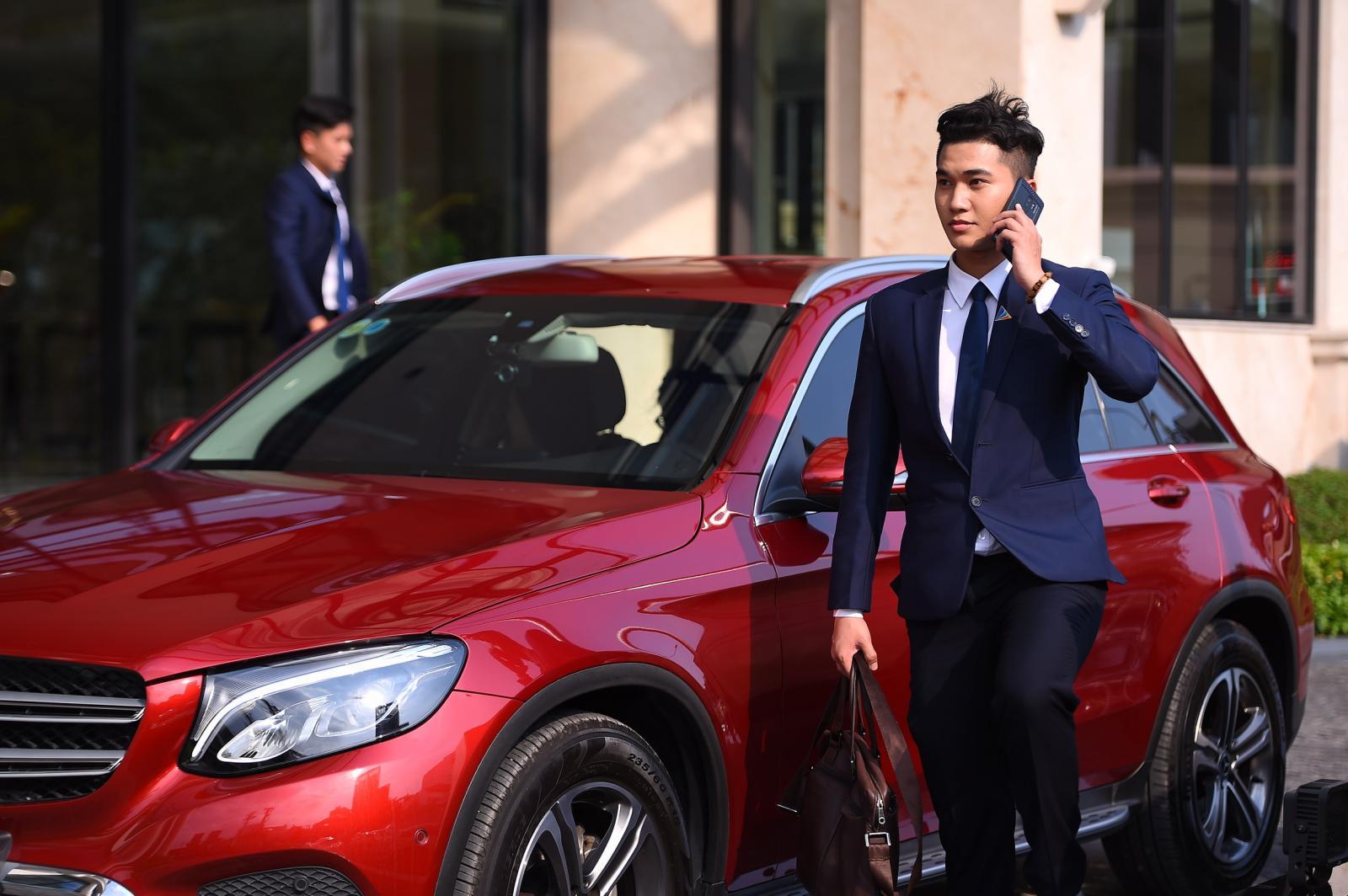 Một nhân viên môi giới bất động sản mặc vest, đang nghe điện thoại cạnh ô tô màu đỏ.