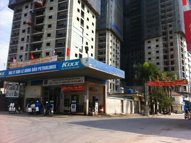 Tòa nhà chung cư cao tầng đang xây dựng, bên dưới là trạm xăng dầu nằm gần con đường lớn.