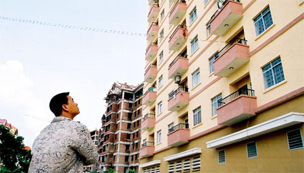 1 người đàn ông ngước lên nhìn 1 tòa nhà chung cư đã cũ